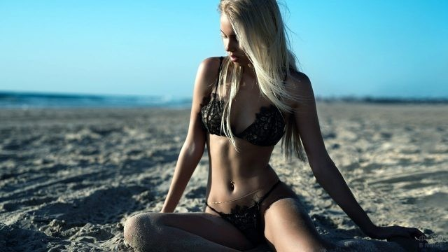Модель в сексуальном чёрном купальнике сидит на песчаном пляже