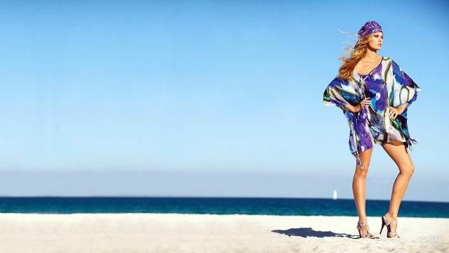 Модель в тунике стоит на пляже у моря