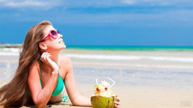 Счастливая девушка с тропическим коктейлем на морском пляже