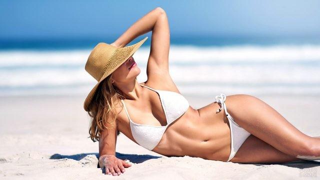 Счастливая туристка в широкополой шляпе и белом купальнике лежит на пляже