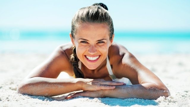 Смеющаяся девушка лежит на песчаном пляже