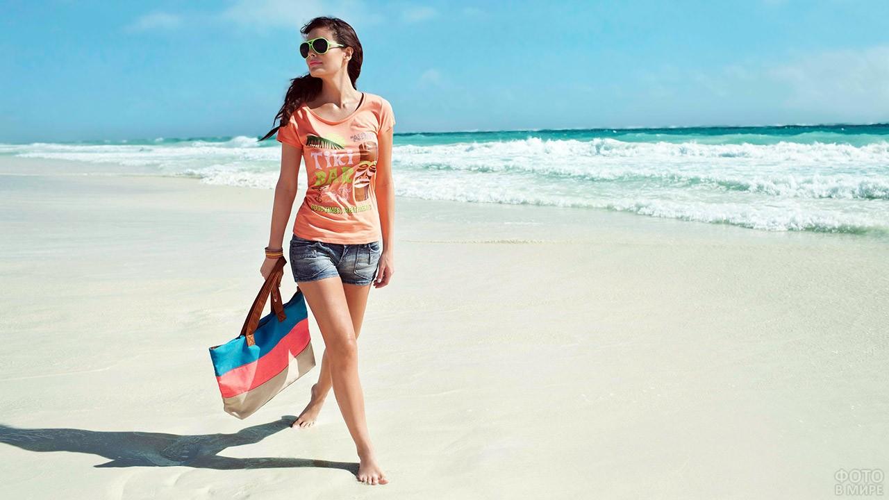 Туристка в шортах и футболке гуляет по морскому пляжу