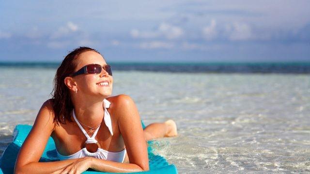 Туристка в солнечных очках лежит на мелководье, подставив лицо солнцу