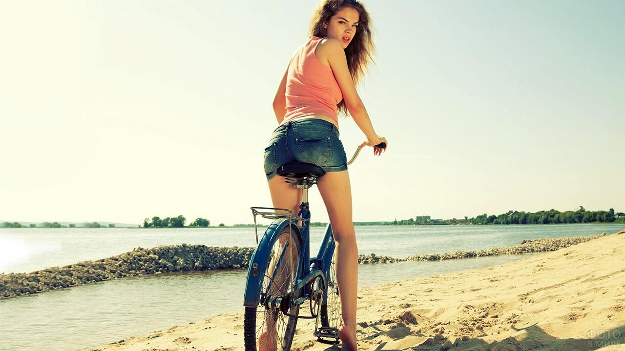 Велосипедистка в шортах на песчаном пляже