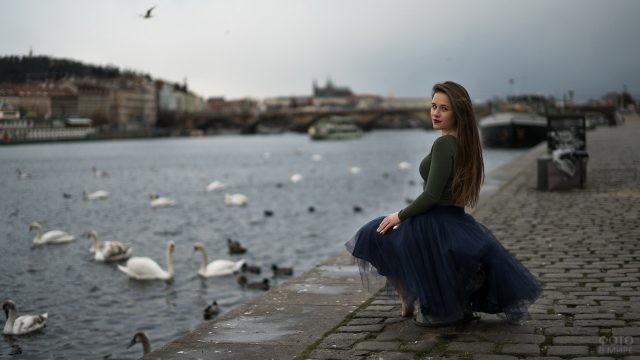 Девушка на набережной на фоне плавающих лебедей
