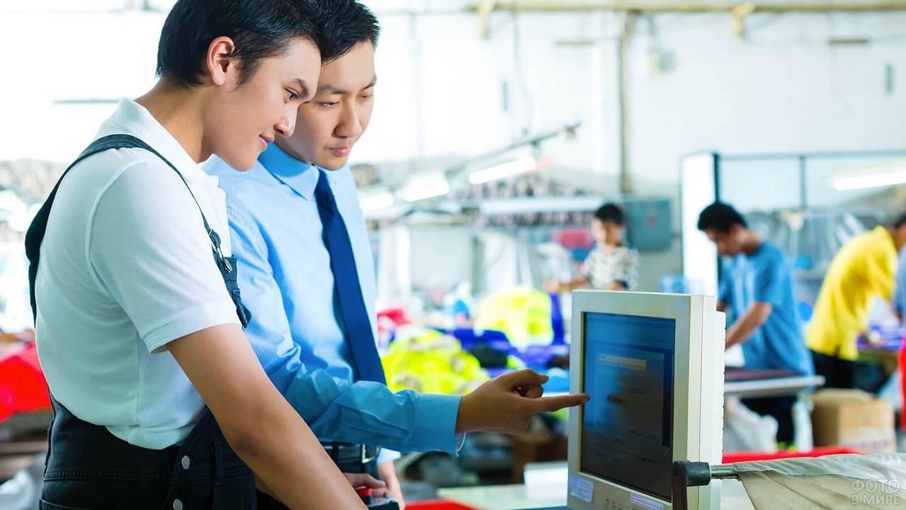 Два азиата работают на автоматизированном станке