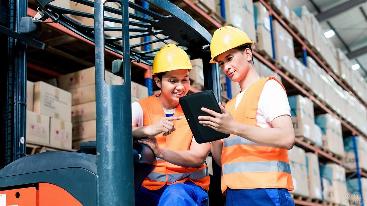 Двое рабочих на погрузчике на складе