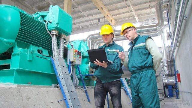 Двое рабочих разговаривают на заводе