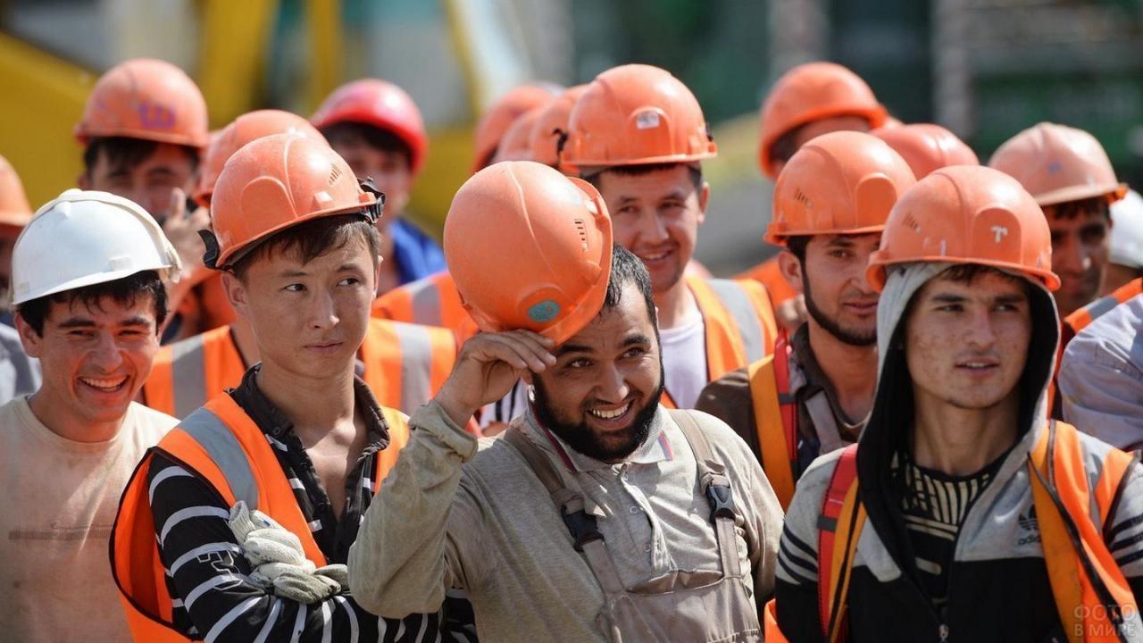 Группа рабочих гастарбайтеров в касках