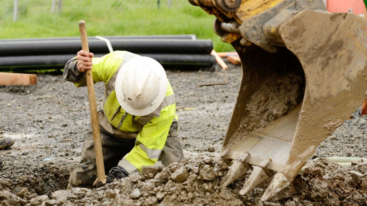 Мужчина в каске копает яму