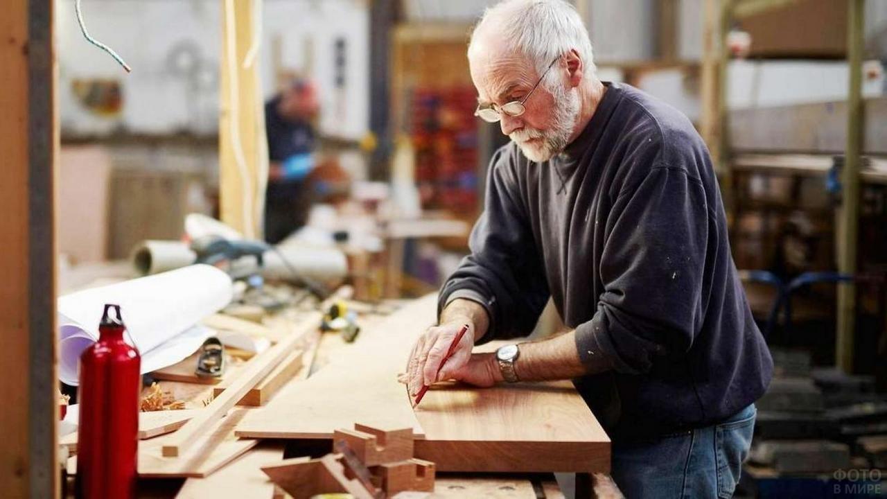 Пожилой столяр с бородой и в очках работает с деревом