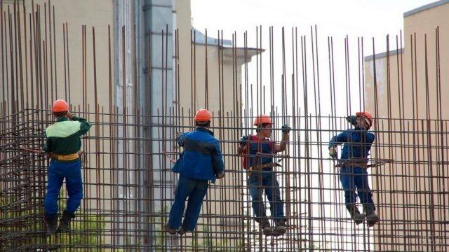 Рабочие бетонщики на обвязке арматуры