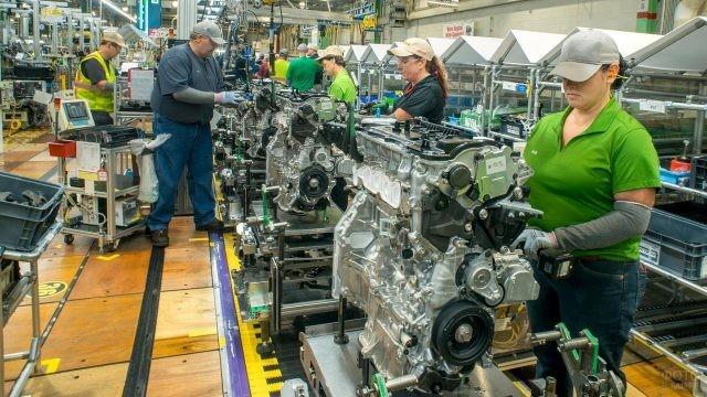 Рабочие собирают автомобильный двигатель
