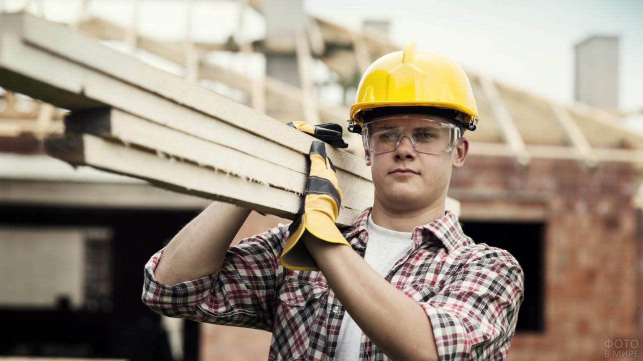 Рабочий в защитных очках держит доски