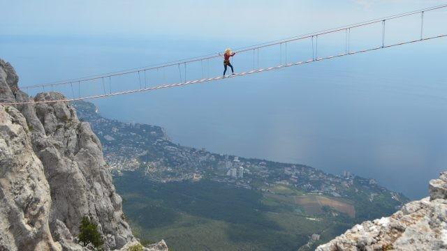 Девушка идёт по верёвочному мосту