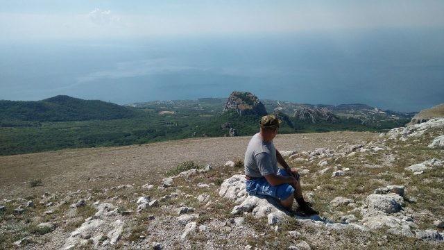 Мужчина сидит на камне в долине горы Ай-Петри