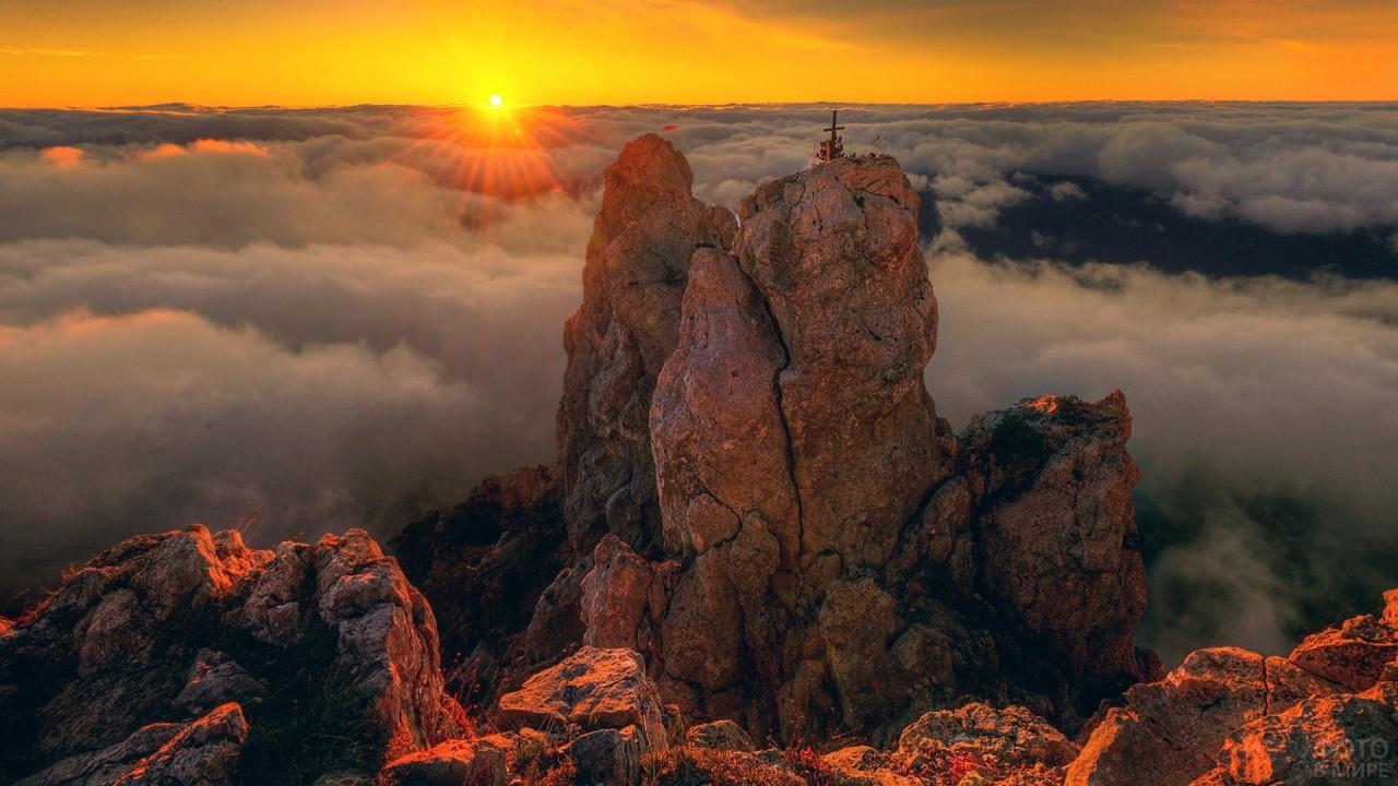 Последние лучи солнца освещают крест на горе Ай-Петри