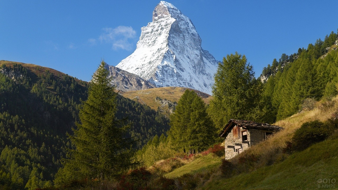 Домик на склоне холма на фоне высокой горы