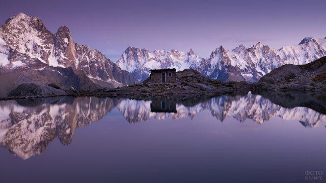 Одинокий дом у воды на фоне гор