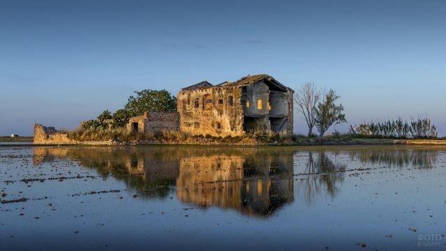 Полуразрушенный дом на берегу озера