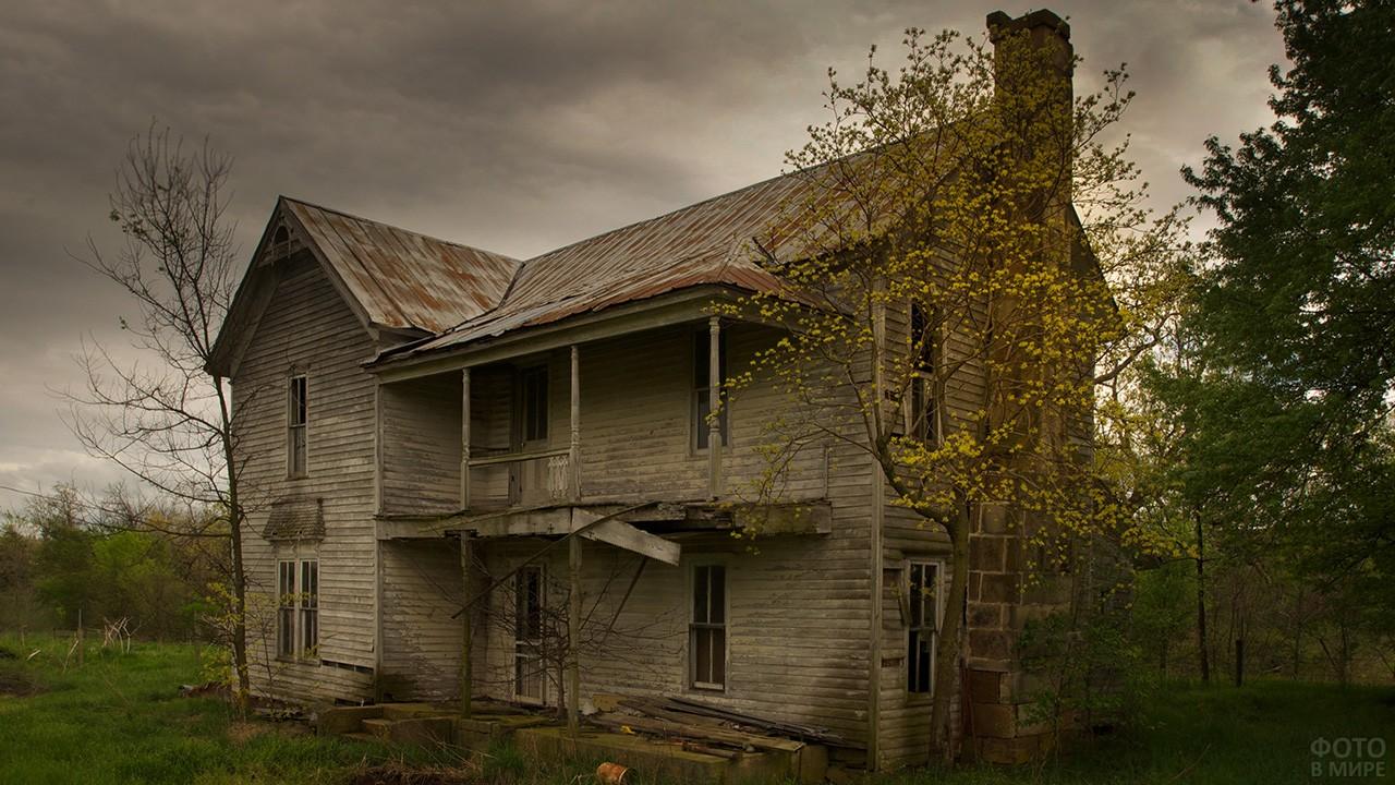 Полуразрушенный дом на фоне серого неба