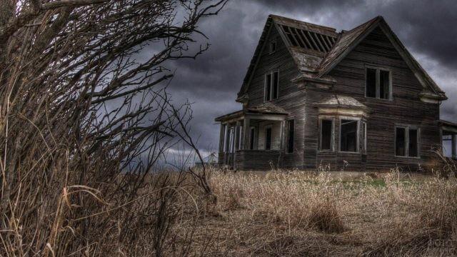 Полуразрушенный дом среди сухих зарослей травы