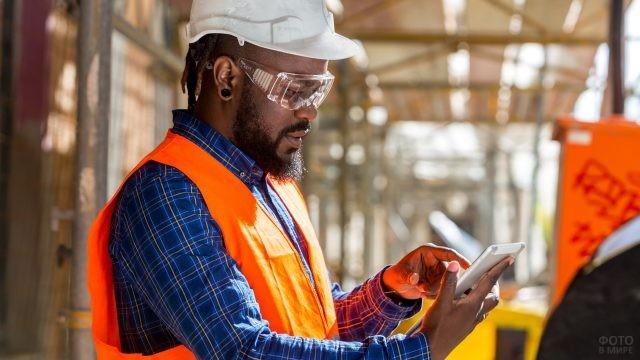 Мужчина в каске и очках держит в руках планшет