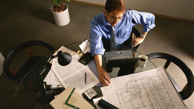 Мужчина за столом с кофе, ноутбуком и чертежами
