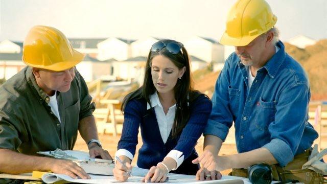 Женщина инженер общается со строителями