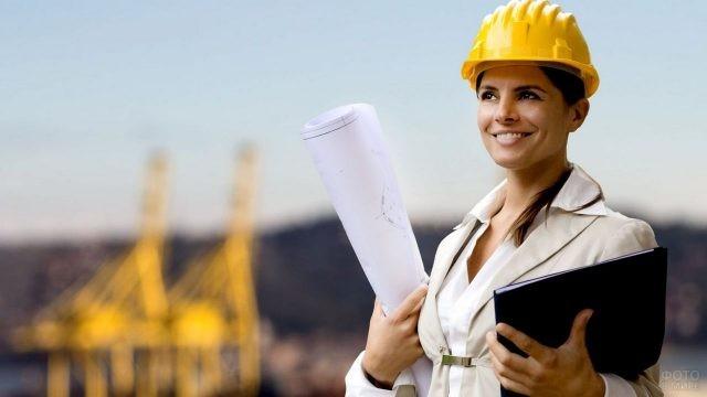 Женщина в каске и с папкой в руках