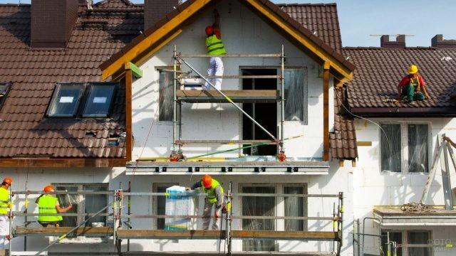 Бригада строителей ремонтирует фасад дома