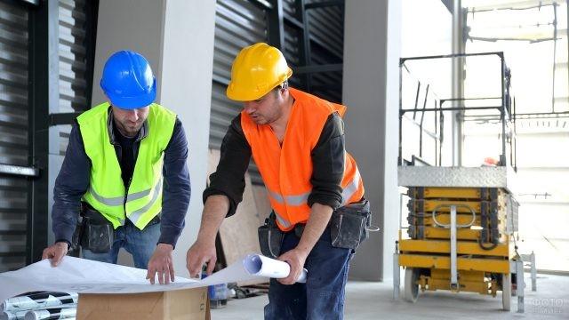 Двое мужчин в касках обсуждают проект на стройплощадке