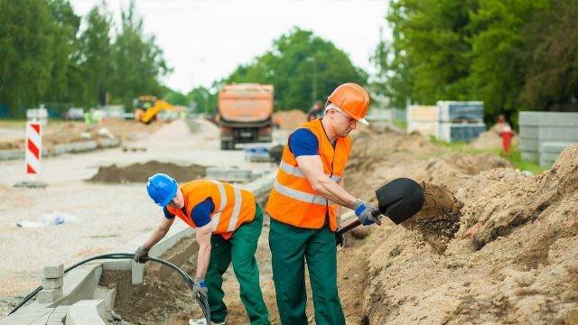 Двое рабочих копают траншею под кабель