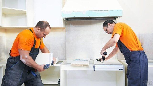Двое строителей собирают мебель в квартире