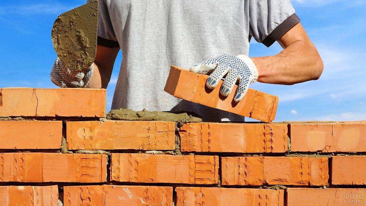Каменщик в перчатках кладёт кирпич