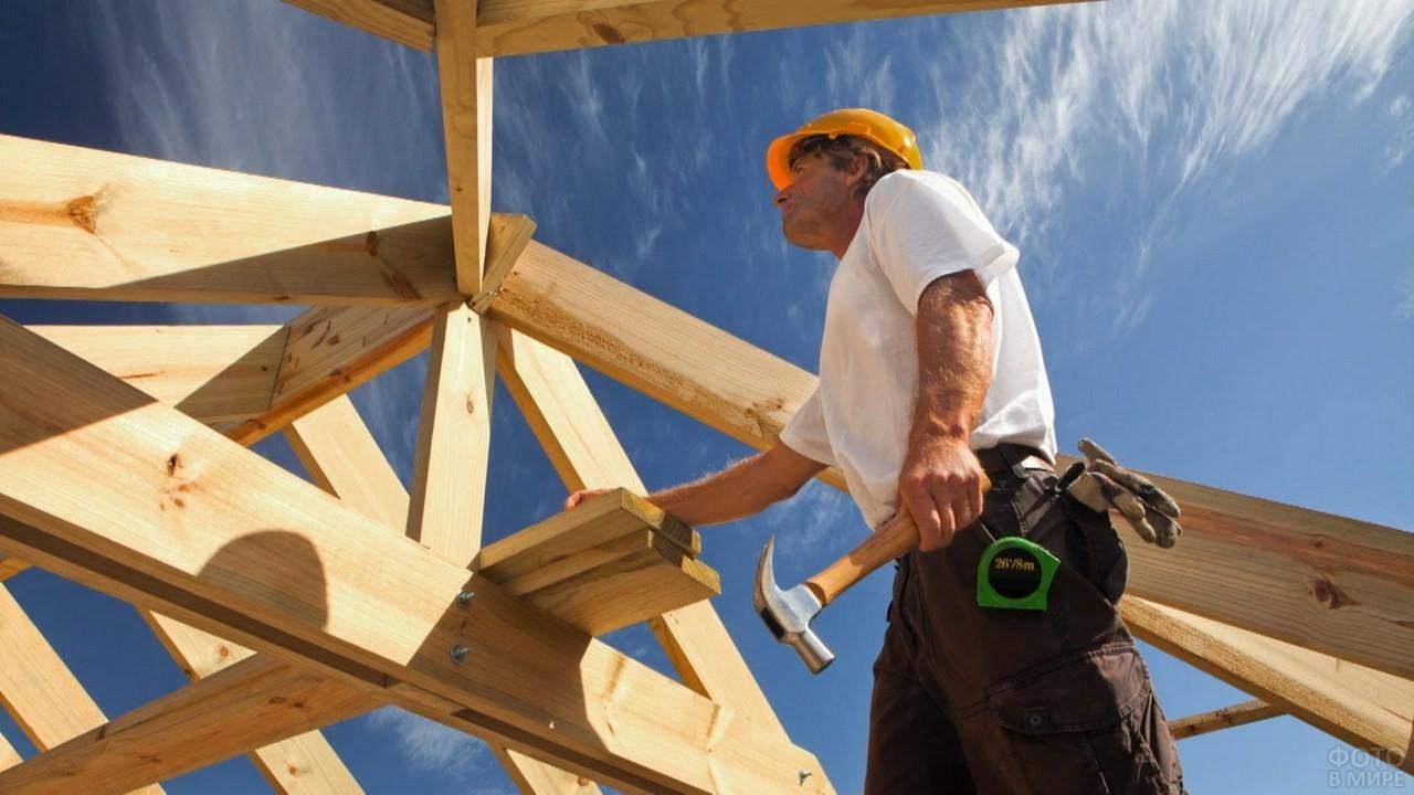 Кровельщик делает деревянный каркас крыши