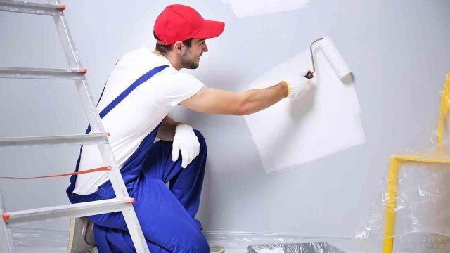 Маляр красит стену валиком в белый цвет