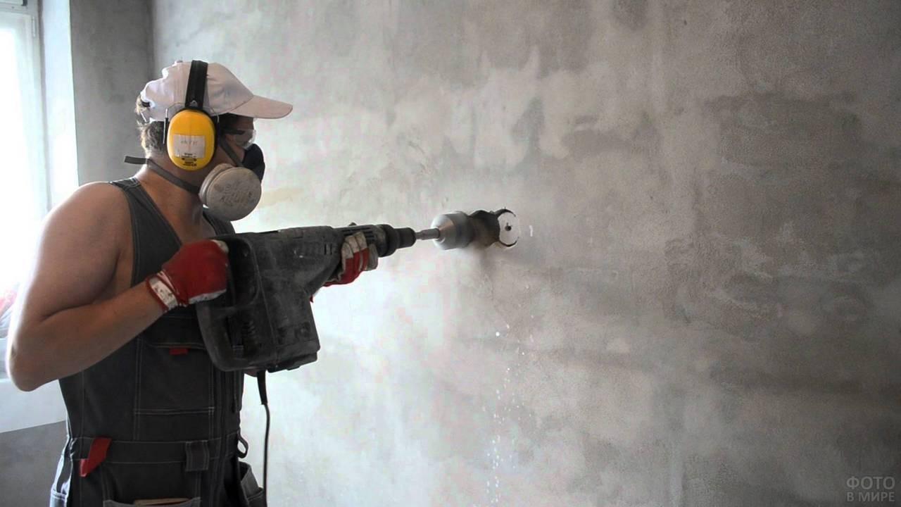 Мужчина штробит стену перфоратором