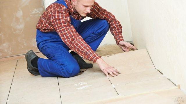 Плиточник укладывает плитку на полу