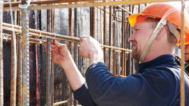 Рабочий на строительной площадке закрепляет арматуру