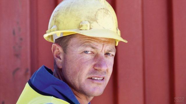 Работник в каске смотрит в камеру