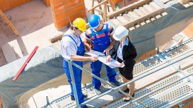 Строители общаются с женщиной-инженером на стройке