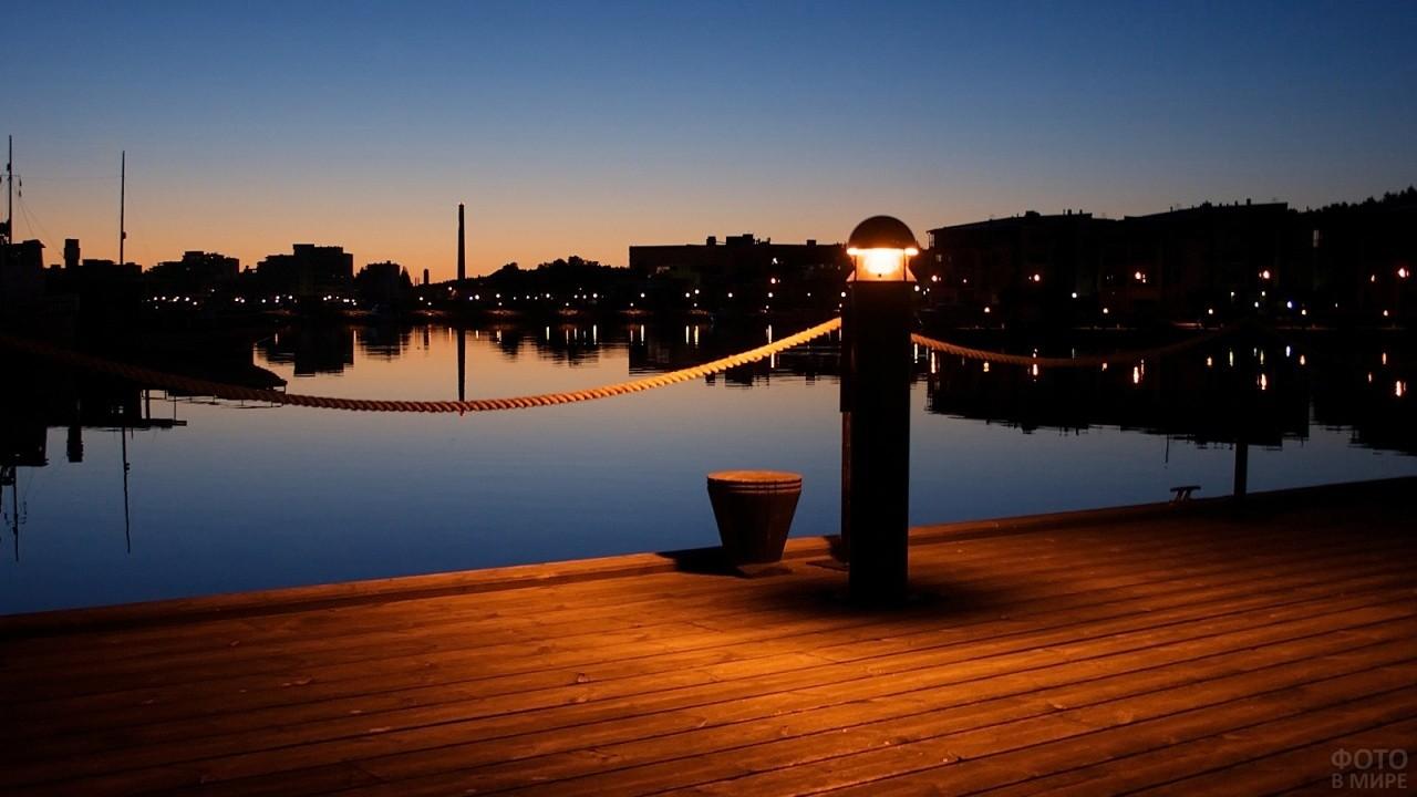 Фонарь на причале на фоне ночного города