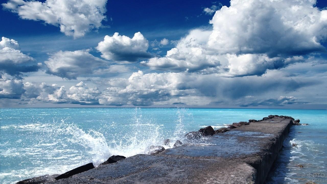 Морские волны разбиваются о каменный причал