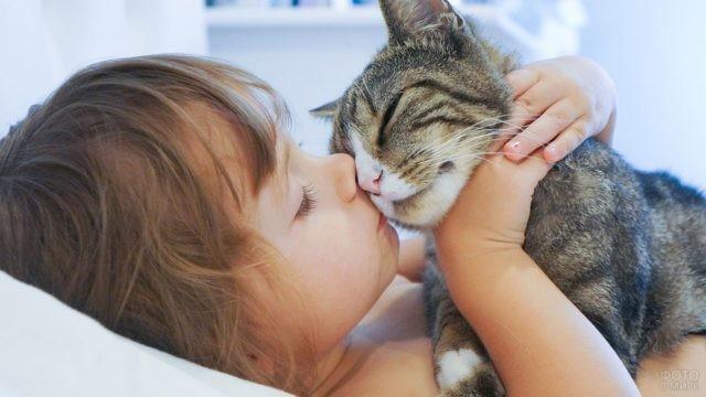 Девочка целует кота