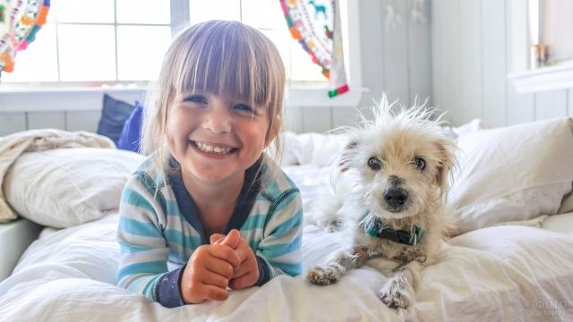 Девочка лежит в кровати с собачкой и улыбается
