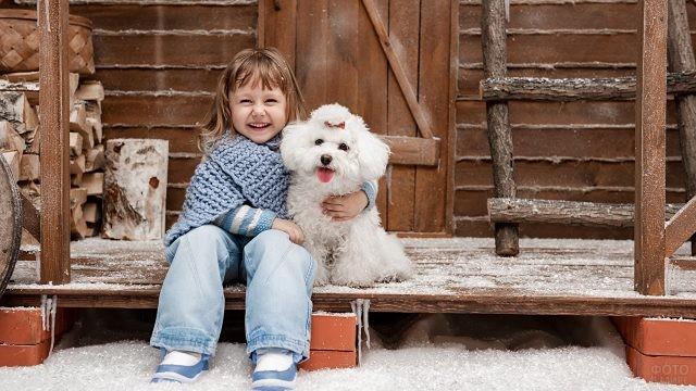 Девочка на веранде обнимает собаку