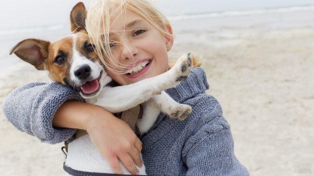 Девочка обнимает собаку возле моря
