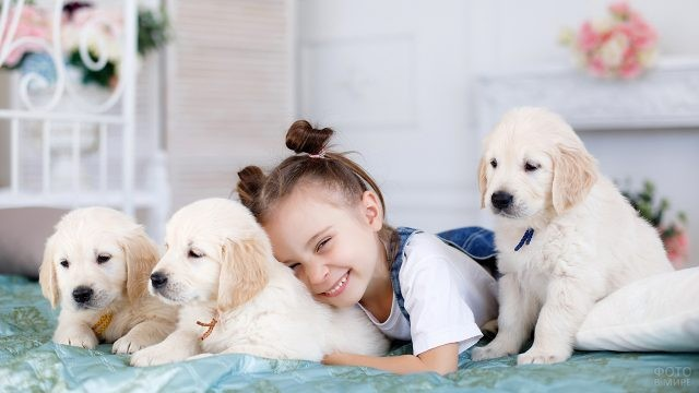 Радостная девочка с белыми щенками