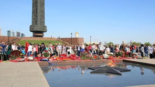 Люди возлагают цветы к Вечному огню на Поклонной горе 9 мая